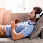 Young male couch listen headphones  mobile phone  at home