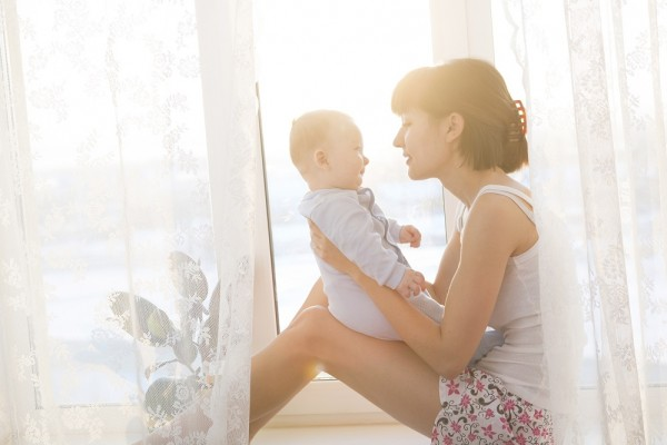 Young mother with a baby in a beautiful bedroom. Happy mother holding adorable child baby with sunrise background