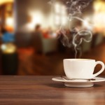 Coffee drink on wooden table with blur cafeteria as background