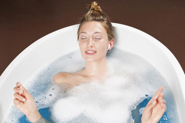 Young woman in bathtub listening to music, elevated view