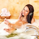 Young woman listening to music in bubble  bath. See soles of  feet