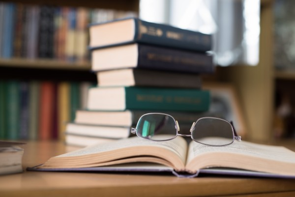Opened Book with Glasses above and a Stack of Books on the Background