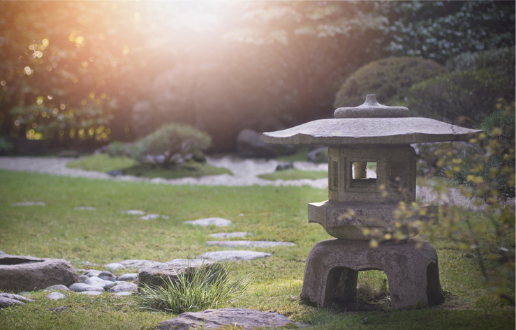 Statue in Japanese Tea Garden, with sun setting in the background.