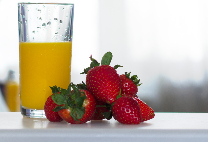 Colour photograph of orange juice and srawberries.
