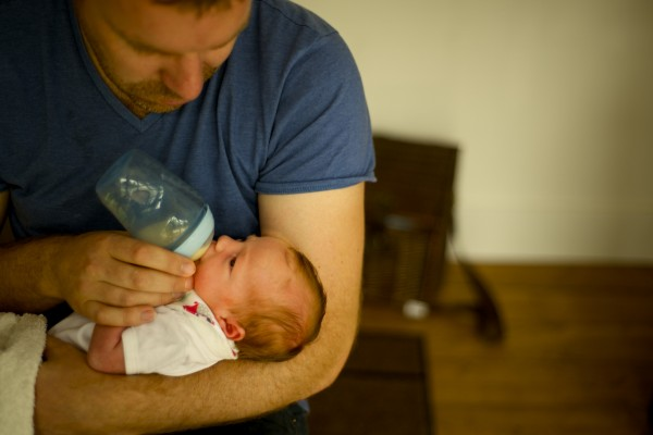 father breastfeeding with baby bottle her little new born daughter