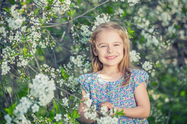 Happy little girl playing in spring cherry garden
