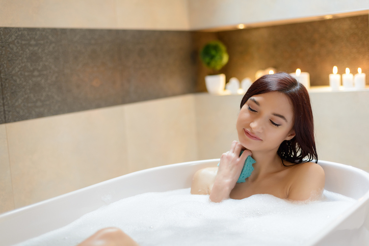 Young brunette woman taking bath