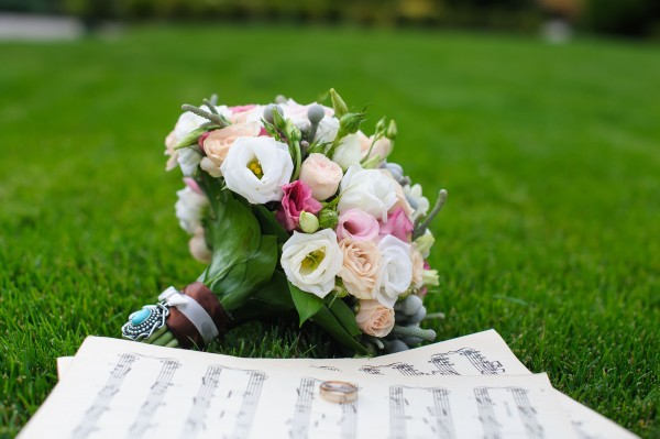 Two wedding rings on a sheet of paper with music notes. Wedding bouquet on the green grass. Wedding concept.