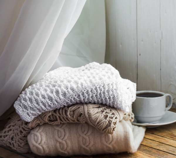 Knit cozy sweater folded in a pile on wooden background near the window . With a Cup of tea and dried lemon.Warm concept.