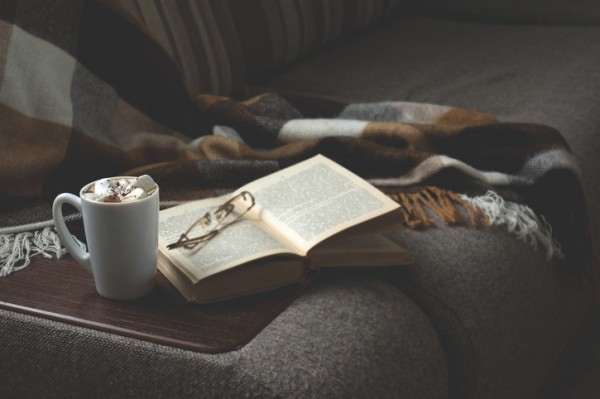 Cup of hot coffee with marmalade book points the blanket