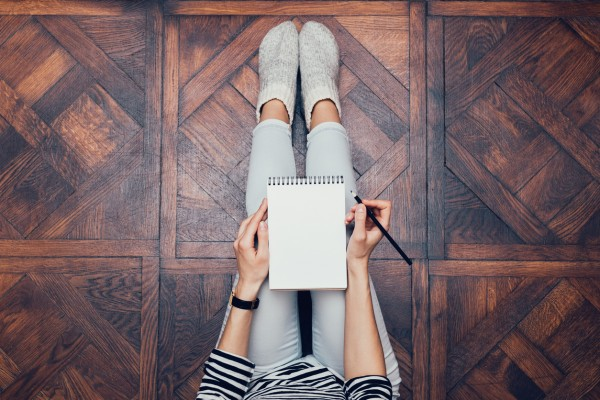 Girl in jeans sitting on the floor at home and writing in a notebook