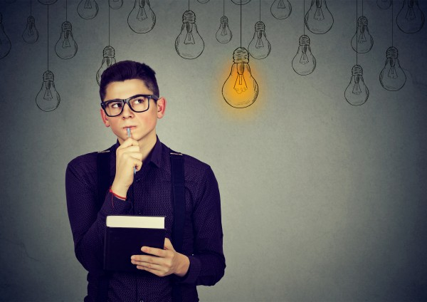 Handsome thinking man in glasses looking up with light idea bulb above head isolated on gray wall background.