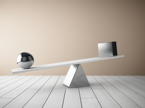 Balancing steel ball and cube on wooden floor in room. 3D illustration.